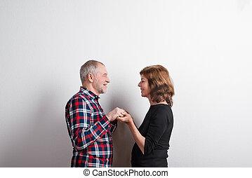 Beautiful senior couple in love holding hands. Studio shot.