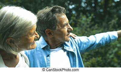 Beautiful senior couple in sunny summer nature.