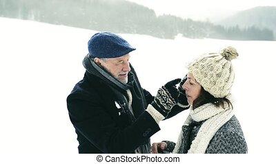 Beautiful senior couple in winter nature.