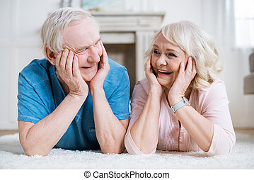 Beautiful senior couple lying on carpet and smiling each other