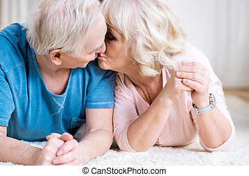 Beautiful senior couple lying on carpet together and kissing
