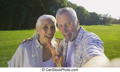 Beautiful senior couple making selfies outdoors - Beautiful...