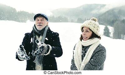 Beautiful senior couple making snowballs in winter nature.