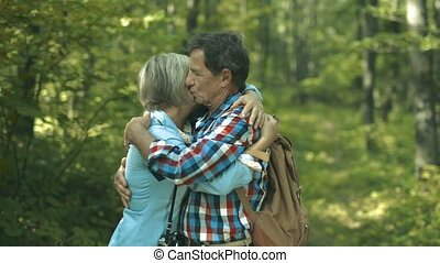 Beautiful senior couple on a walk in sunny summer forest