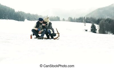 Beautiful senior couple on sledge drinking tea, winter day...