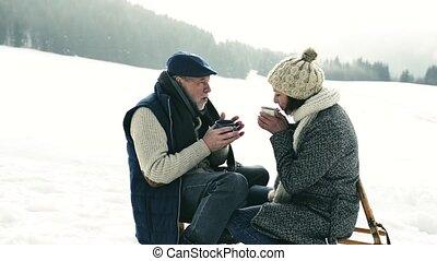 Beautiful senior couple on sledge drinking tea, winter day.