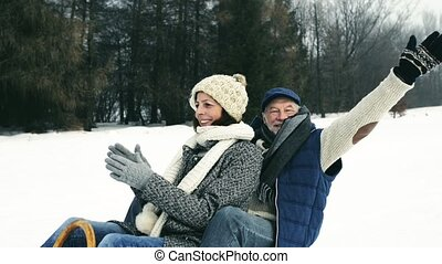 Beautiful senior couple on sledge having fun, winter day. - ...