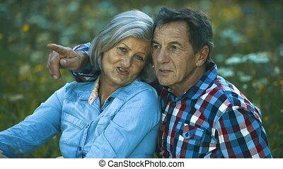 Beautiful senior couple sitting on summer meadow.