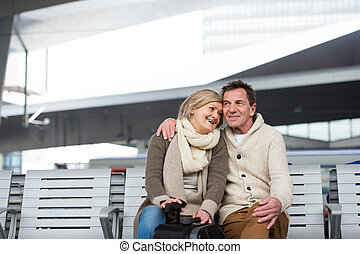 Beautiful senior couple waiting on train station, hugging