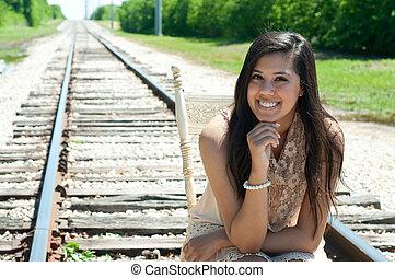 Beautiful senior girl sitting on train tracks.