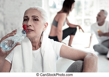 Beautiful senior lady drinking water after training hard