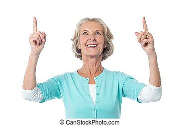 Beautiful senior lady pointing upwards - Cheerful old lady...