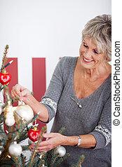 Beautiful senior woman decorating a tree