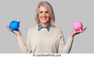 senior woman holding two piggy banks - Beautiful senior...