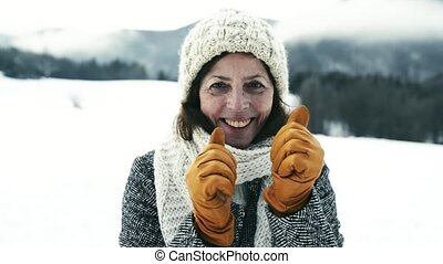 Beautiful senior woman on a walk in winter nature.