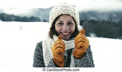 Beautiful senior woman on a walk in winter nature.