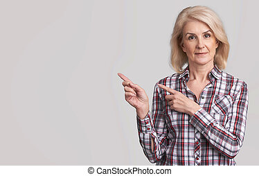 beautiful senior woman pointing to copy space