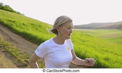 Beautiful senior woman running outside on green hills.