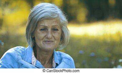 Beautiful senior woman sitting on summer meadow.