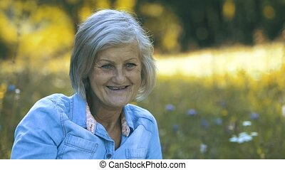 Beautiful senior woman sitting on summer meadow.