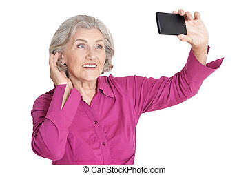 Beautiful senior woman taking selfie with smartphone on white background