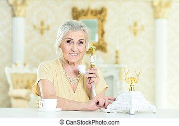 Beautiful senior woman talking on retro phone at home