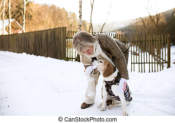 Beautiful senior woman with dog outdoors on sunny winter day