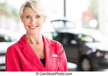 senior woman working at car dealership