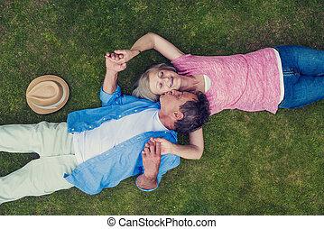 Beautiful seniors in nature - Beautiful seniors lying on a...