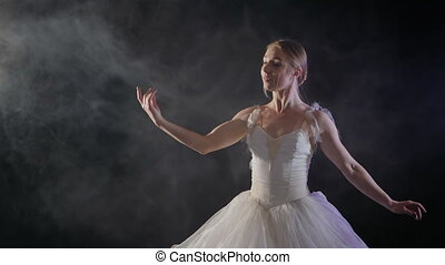 Beautiful sensual ballerina in white tutu dress dancing elements of classical or modern ballet in the dark with light and smoke on the black background, slow motion.