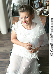 sensual bride in white lace wedding dress posing at home