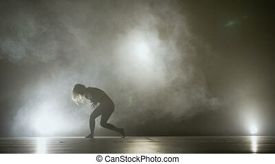 Beautiful sensual female dancing on a smoky stage while auditioning for a prestigious school modern dance