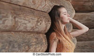 Beautiful sensual young girl with long hair and in a dress posing near a wooden wall from wide logs. Relaxation. Summer. The youth.
