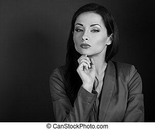 Beautiful serious business woman in grey suit thinking on dark background with empty copy space. Black and white portrait. Closeup