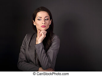 Beautiful serious business woman in grey suit thinking on dark grey background with empty copy space