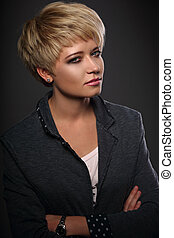 Beautiful serious business woman with short bob blond hair style in fashion jacket on grey background. Closeup portrait