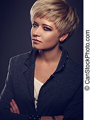 Beautiful serious business woman with short bob blond hair style in fashion jacket on grey background. Closeup toned portrait