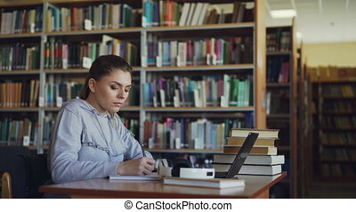 Beautiful serious caucasian female student sitting at table...