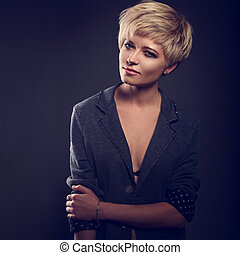 Beautiful serious sexy woman with short bob blond hairstyle in suit on grey background. Closeup portrait. Toned. Fashion