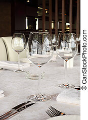 beautiful serving at table with white tablecloth in restaurant; glasses