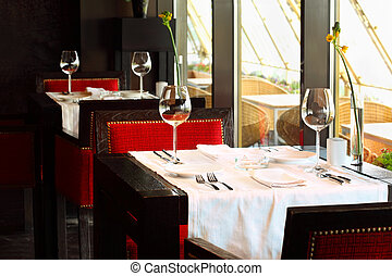 beautiful serving at tables with white tablecloth and red chairs in empty restaurant