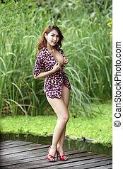 Beautiful sexy Asian girl posing topless outdoors