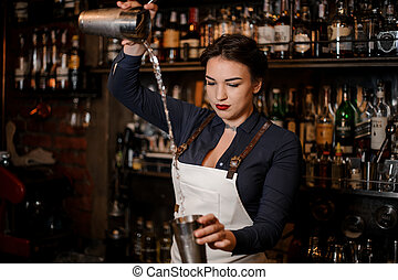 Beautiful sexy barmaid making a fresh summer cocktail -...