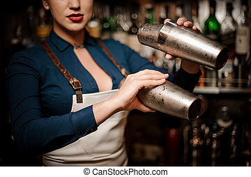 Beautiful sexy barmaid making cocktail in shaker