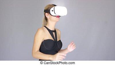 Beautiful sexy blond girl enjoys virtual reality glasses