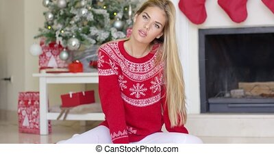 Beautiful sexy blond girl sitting next to christmas tree