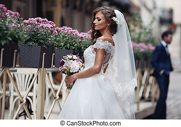 Beautiful sexy blonde bride in elegant white dress with bouquet posing near restaurant with flowers in baskets