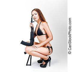 Beautiful sexy blonde girl in bikini holding airsoft gun