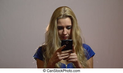 Beautiful Sexy Blonde Girl in Blue Dress Chatting with Phone in Studio