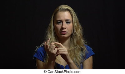 Beautiful Sexy Blonde Girl in Blue Dress Counting on fingers in Studio with black Background.